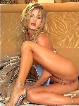 Hot blonde posing on the couch and touching herself