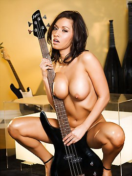 Lana Lopez rocks out at a local music shop - making some sweet music playing a brand new Lyon by Washburn electric bass guitar while sliding it up and down her hot naked body.